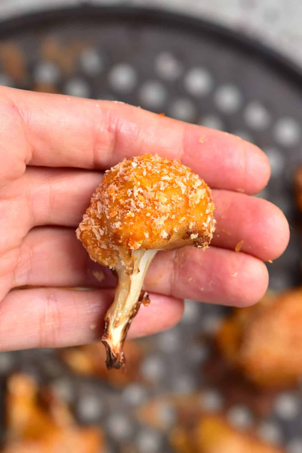 A hand holding one baked breaded cauliflower wing
