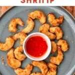 A plate with crispy baked shrimp and a small bowl with chili sauce