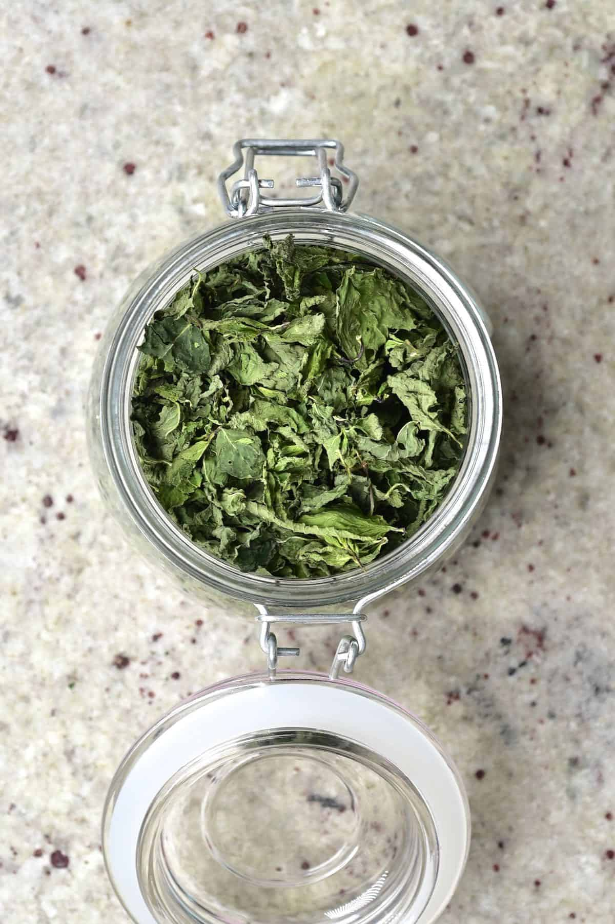 An open jar with dried mint leaves