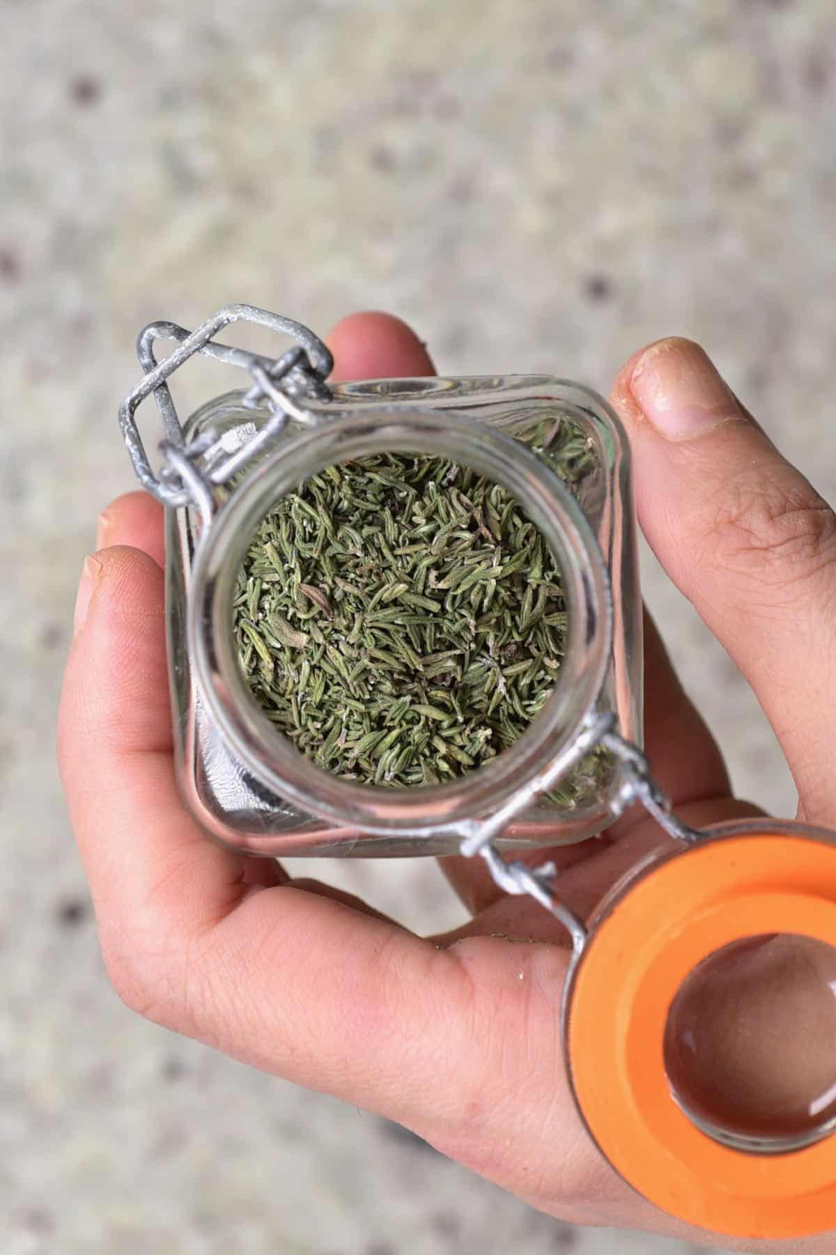 A hand holding a little jar with homemade dried thyme