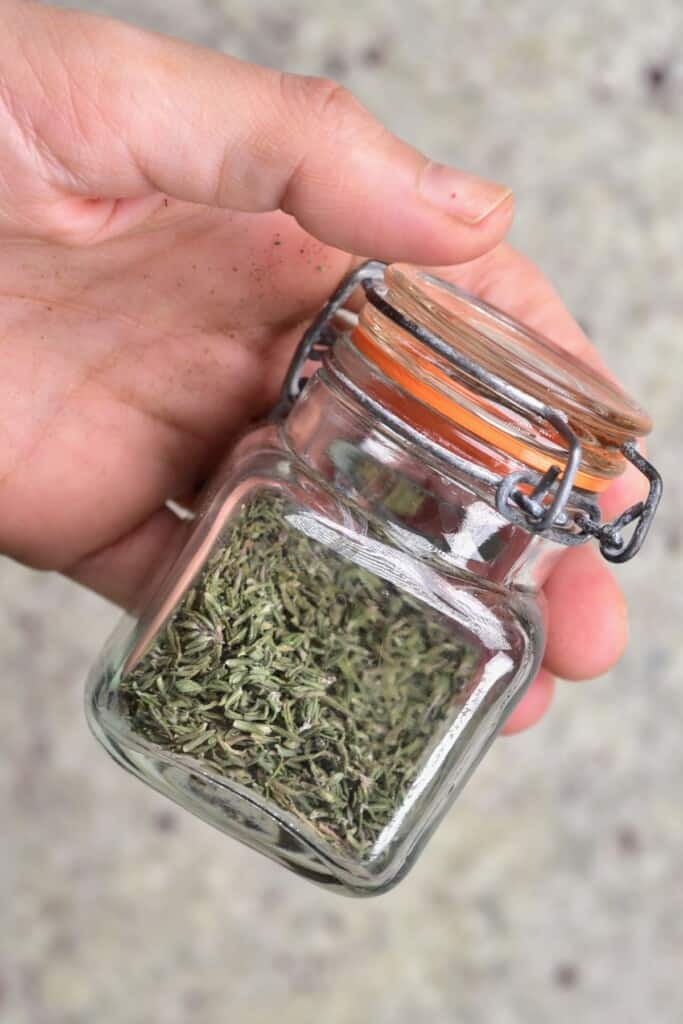 A hand holding a closed little jar with homemade dried thyme