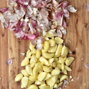 Peeled garlic cloves and their skins on the side