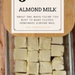 Frozen almond butter cubes in a glass container