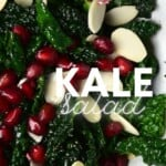 A close up of kale salad with pomegranate seeds and flaked almonds