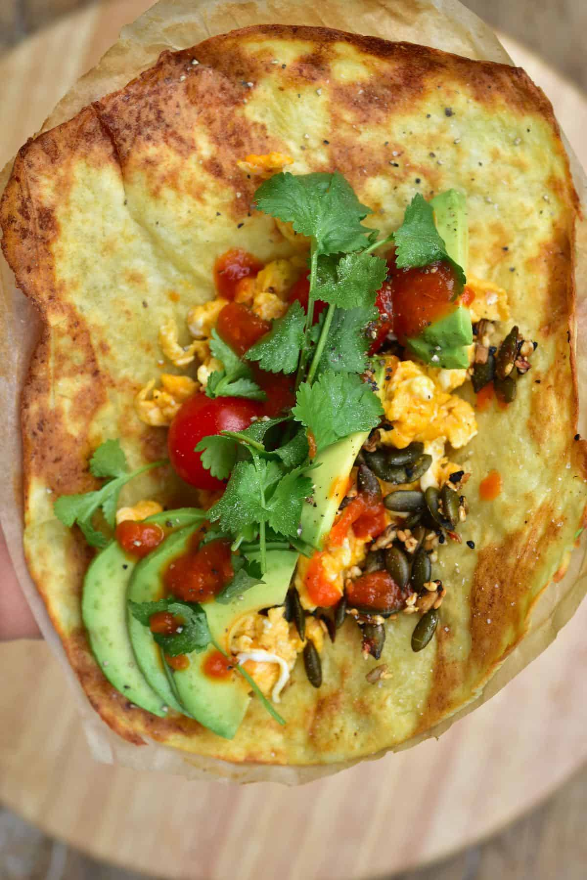 Potato flatbread topped with avocado tomatoes seed mix and cilantro