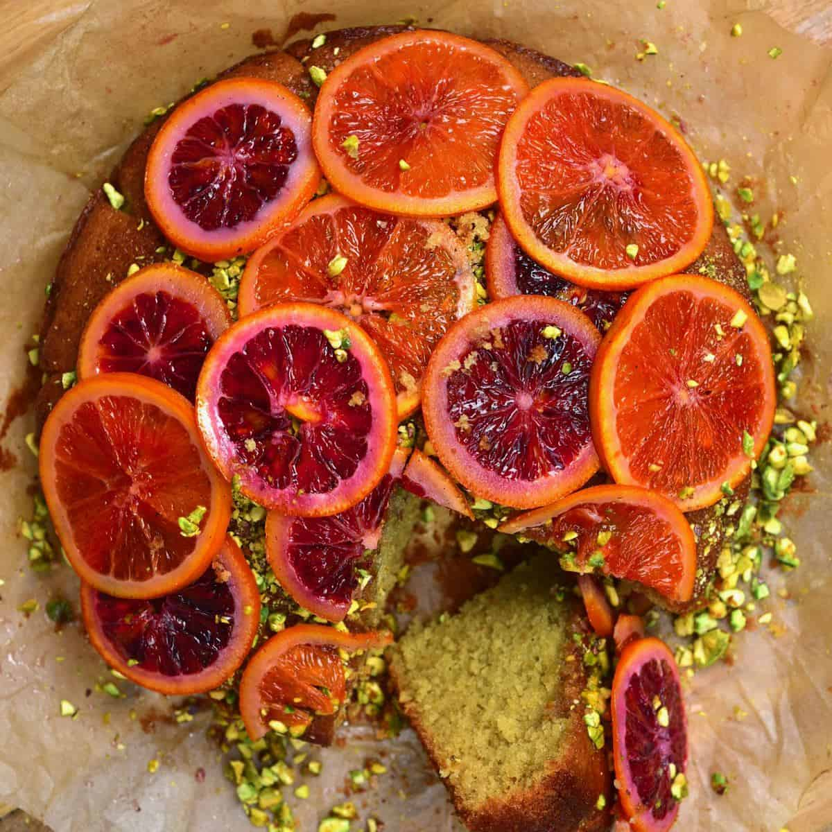 Blood Orange Cake with Pistachios with a piece sliced off