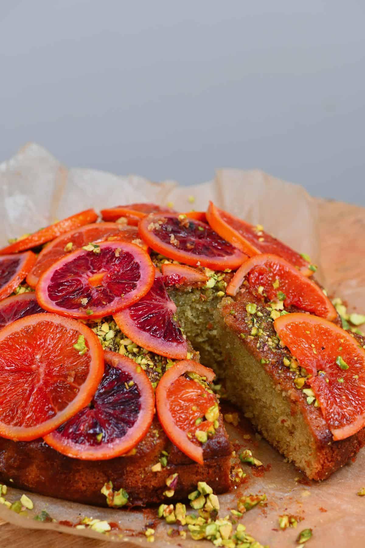 An orange pistachio cake with a slice cut off