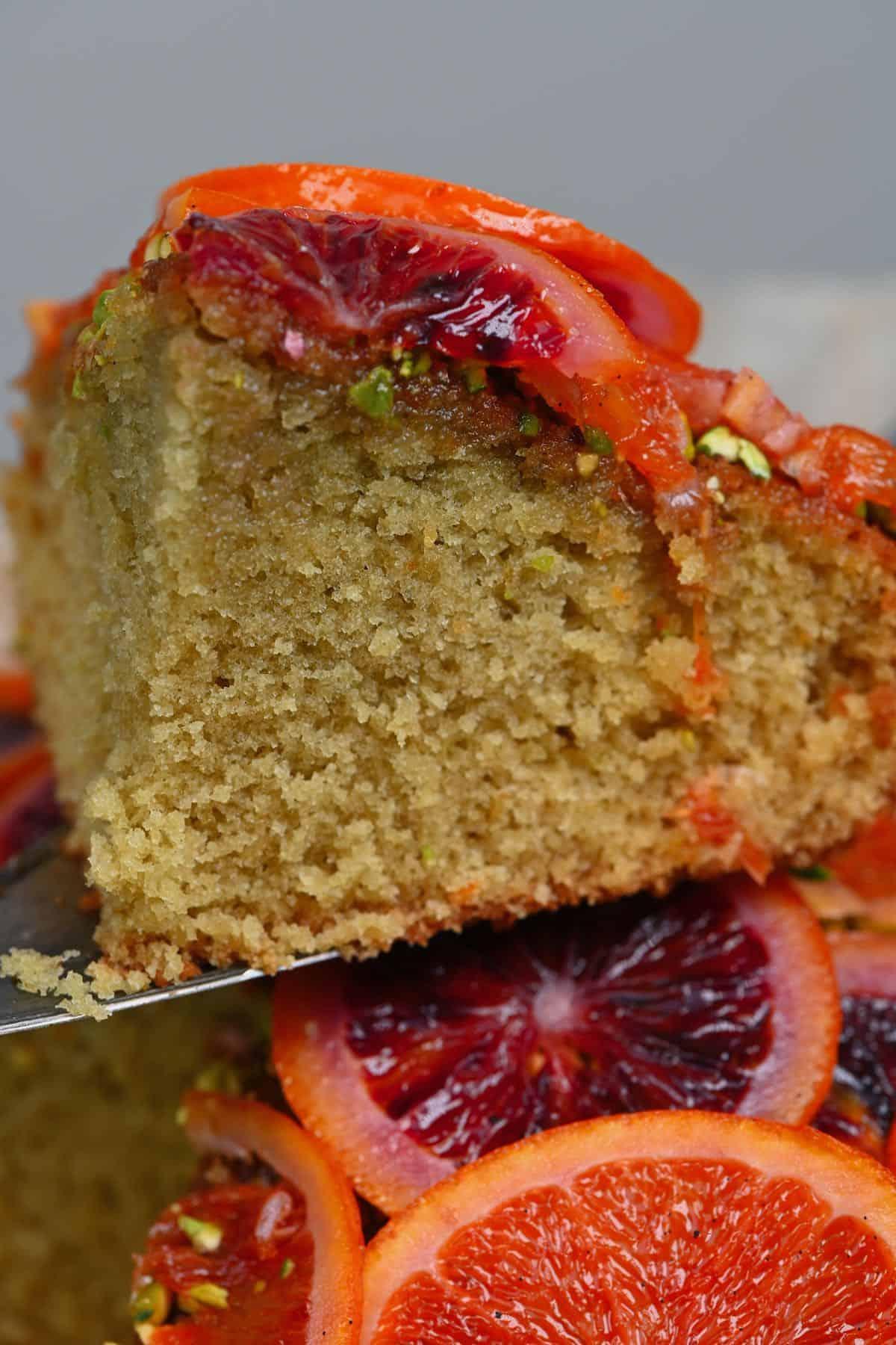 A close up of a slice of orange pistachio cake