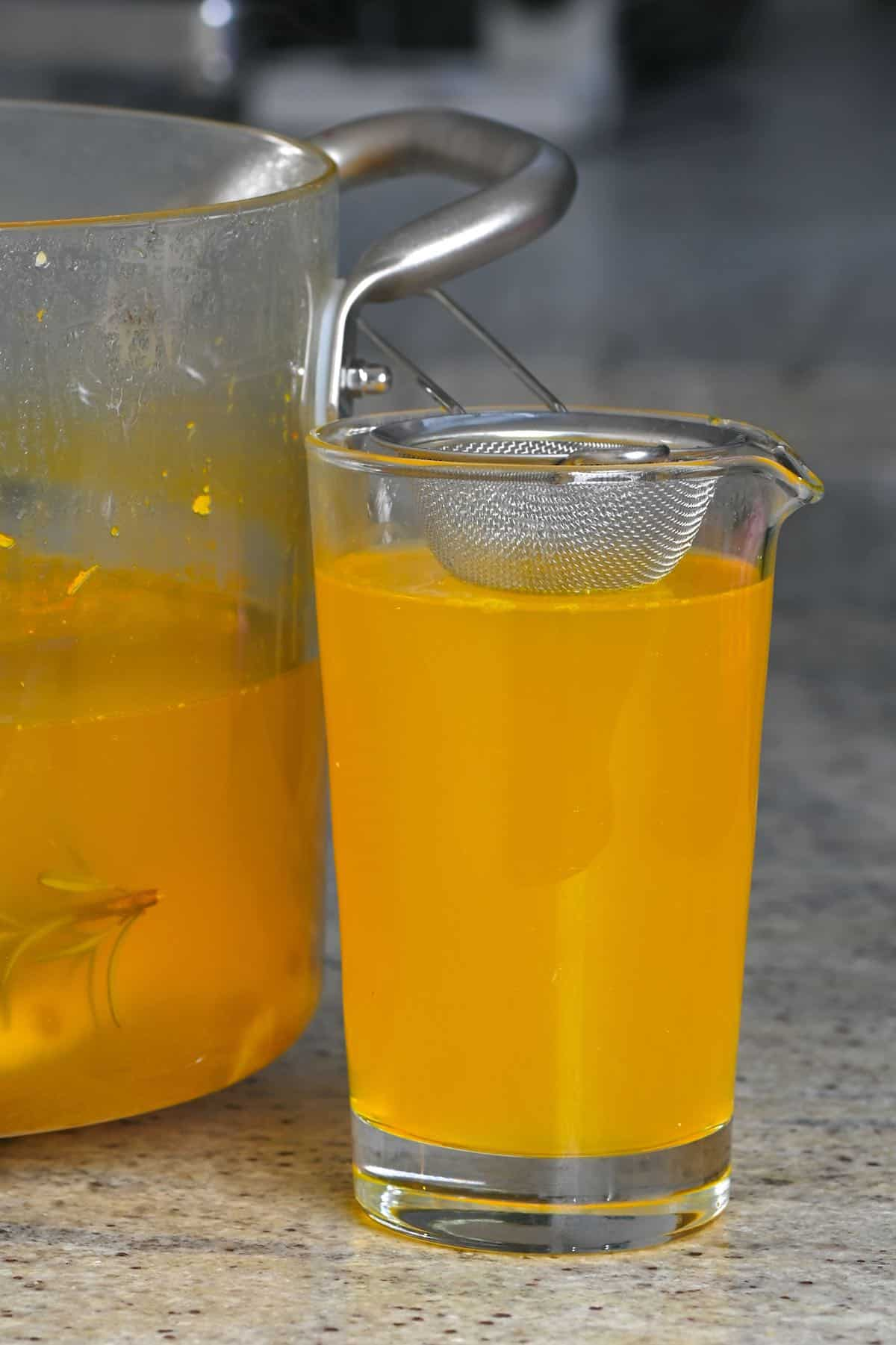 A jug with a small sieve filled with pineapple tea