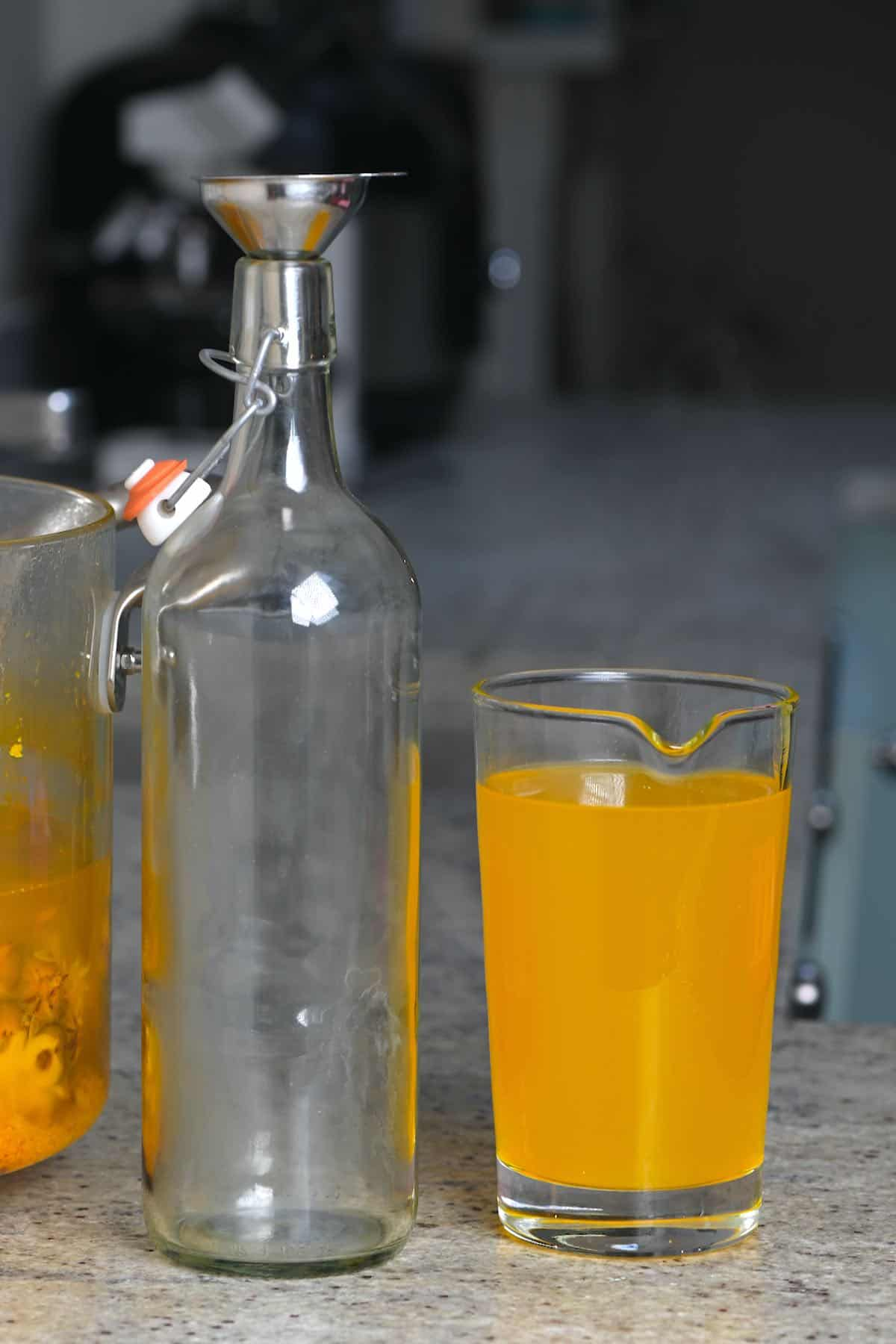 An empty bottle with funnel and a jug filled with pineapple tea