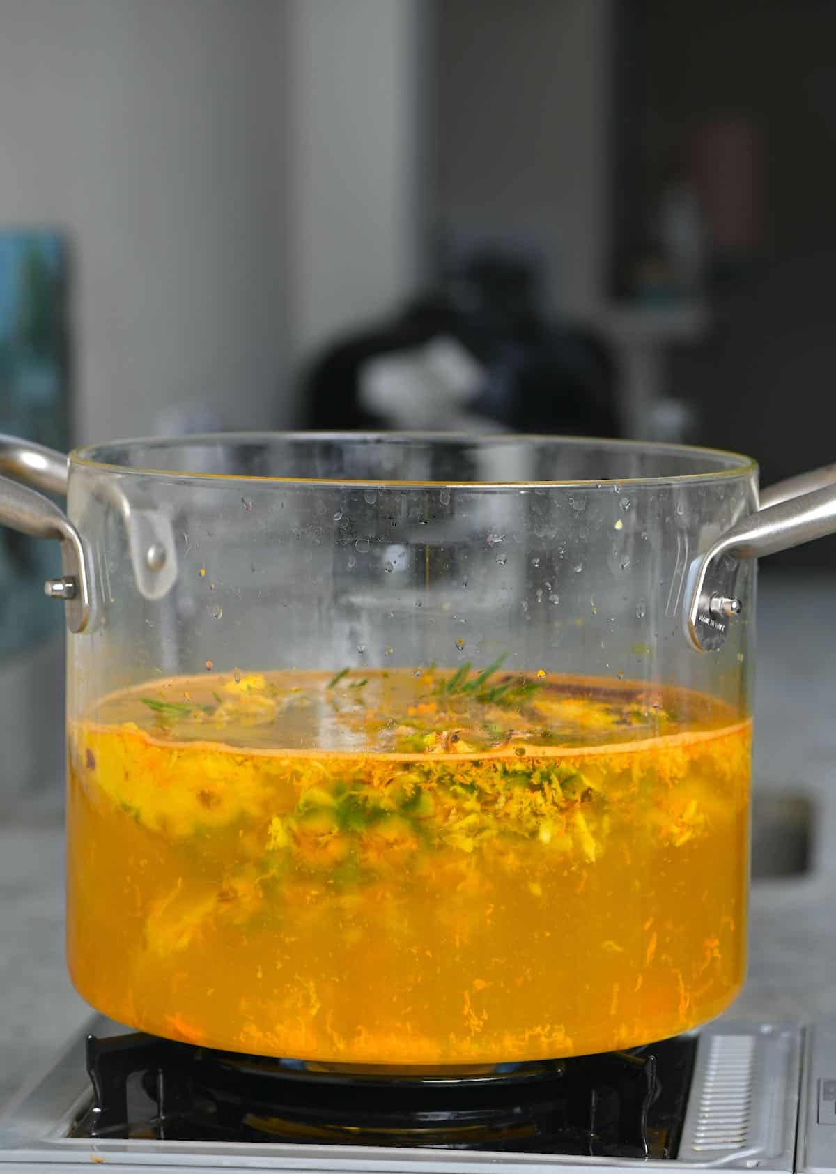 A large glass pot with pineapple peel tea