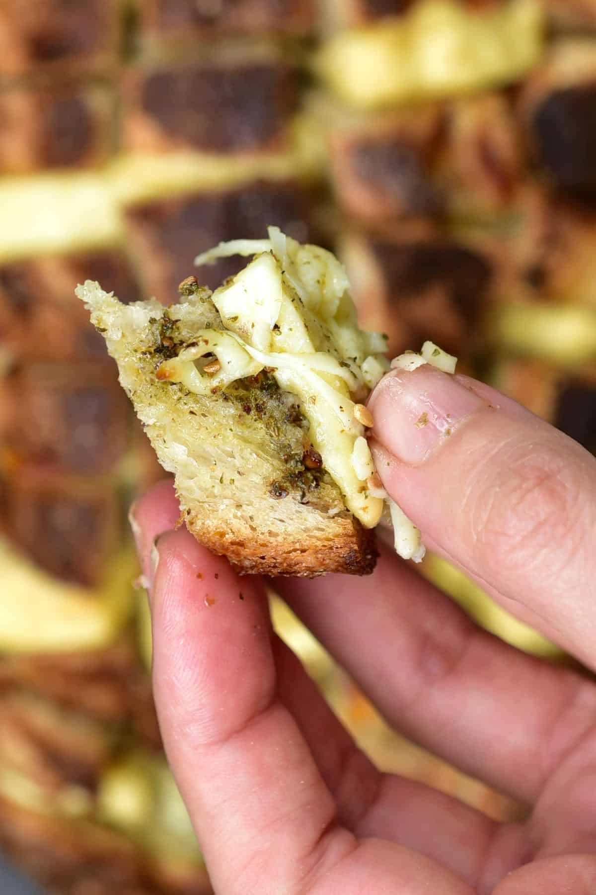 A hand holding a piece of pull-apart bread stuffed with cheese