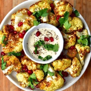 Roasted air fryer cauliflower served in a plate with a small bowl of sauce