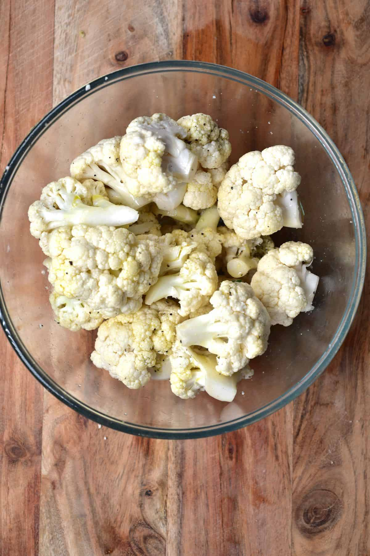 Cauliflower florets coated with oil and spices in a glass bowl