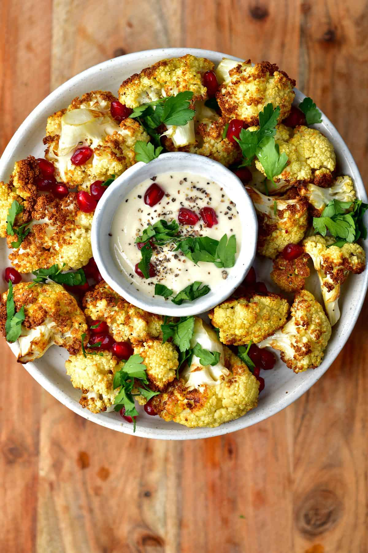 A serving of air fryer cauliflower topped with pomegranate seeds and parsley and a small bowl with tahini sauce