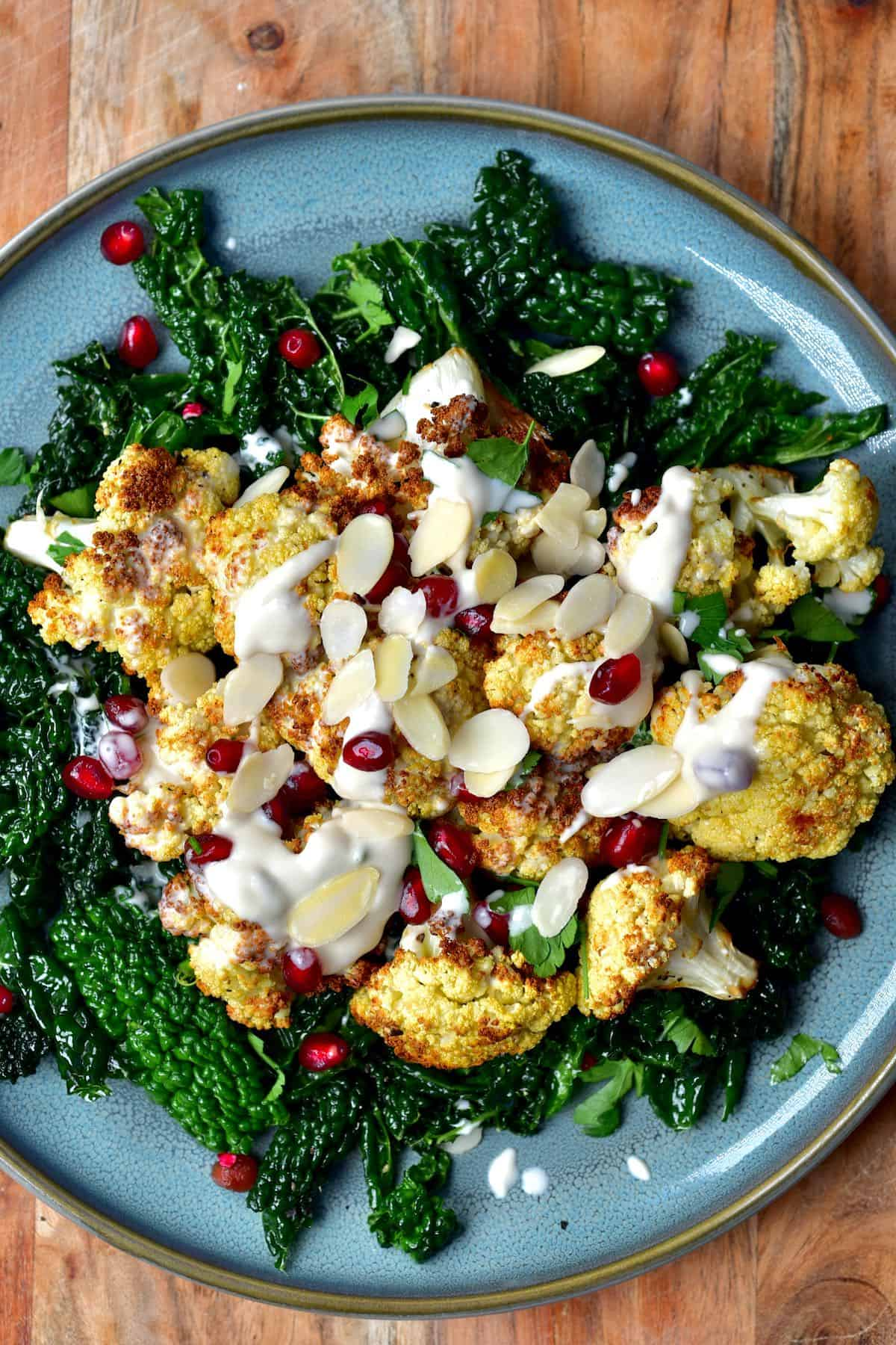 A serving of kale salad and baked cauliflower topped with pomegranate seeds and tahini sauce