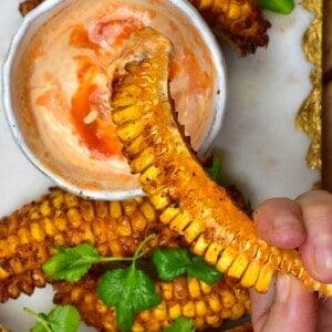 Dipping a spicy corn rib into chili mayo