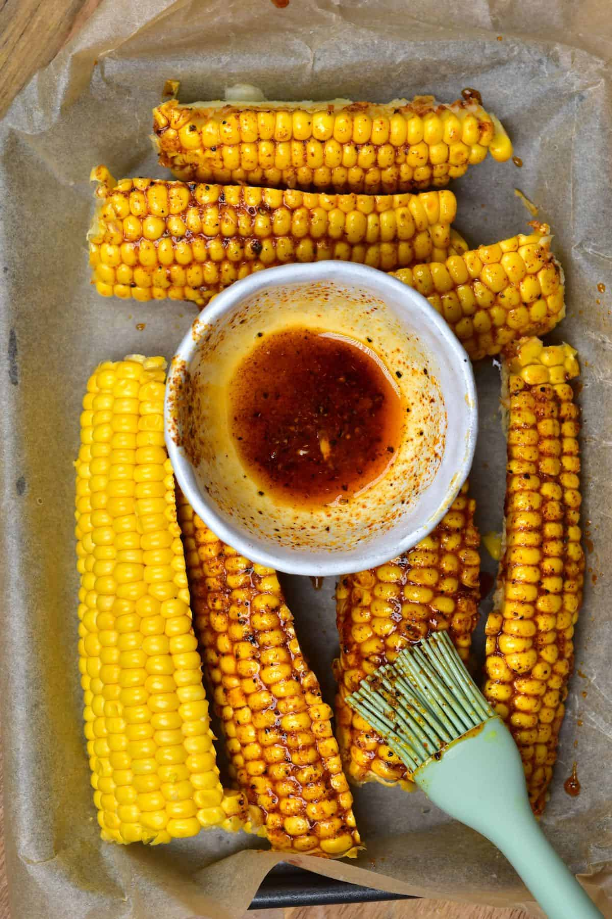 Brushing oil on corn in a baking tray