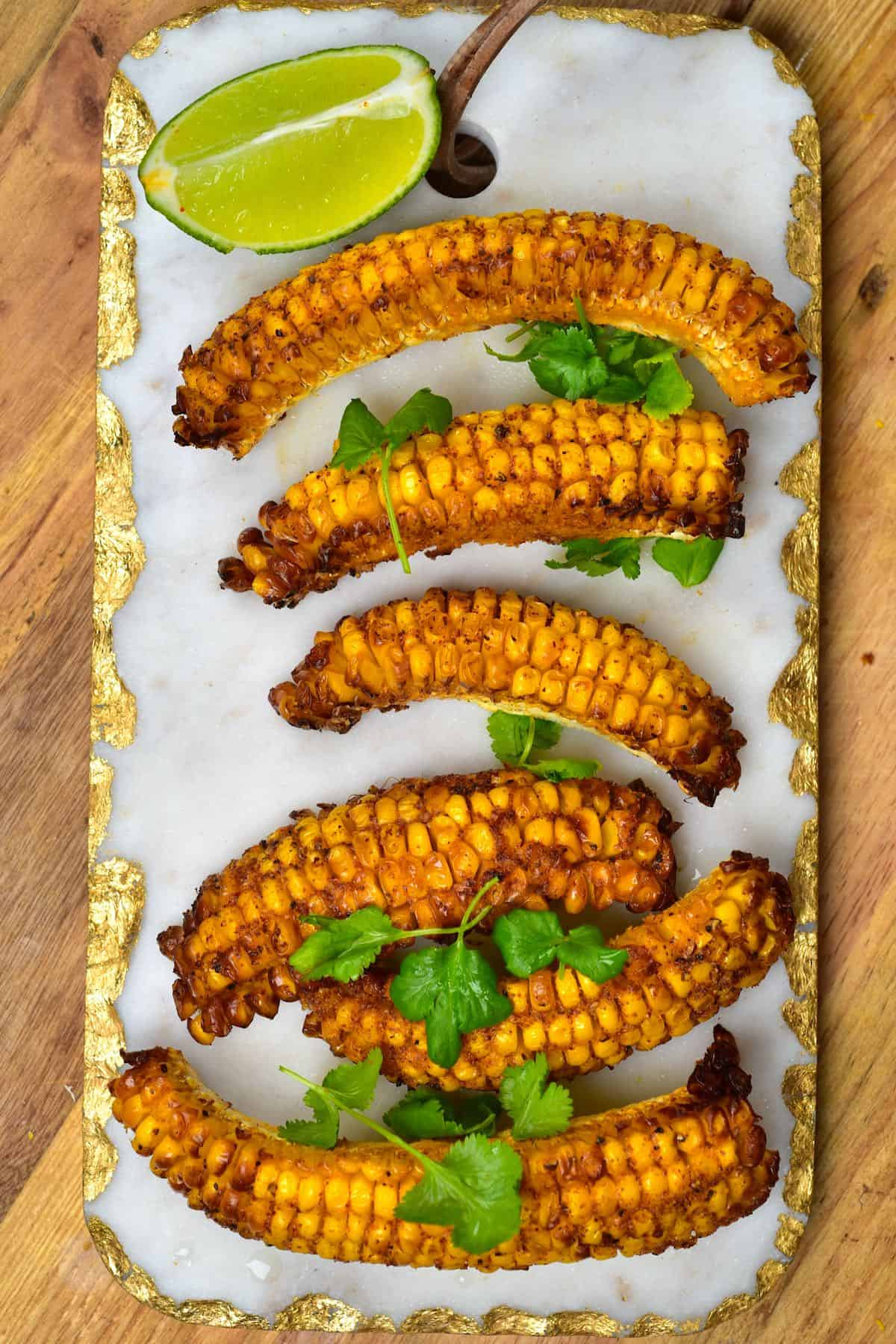 Baked corn ribs on a chopping board with lime and cilantro