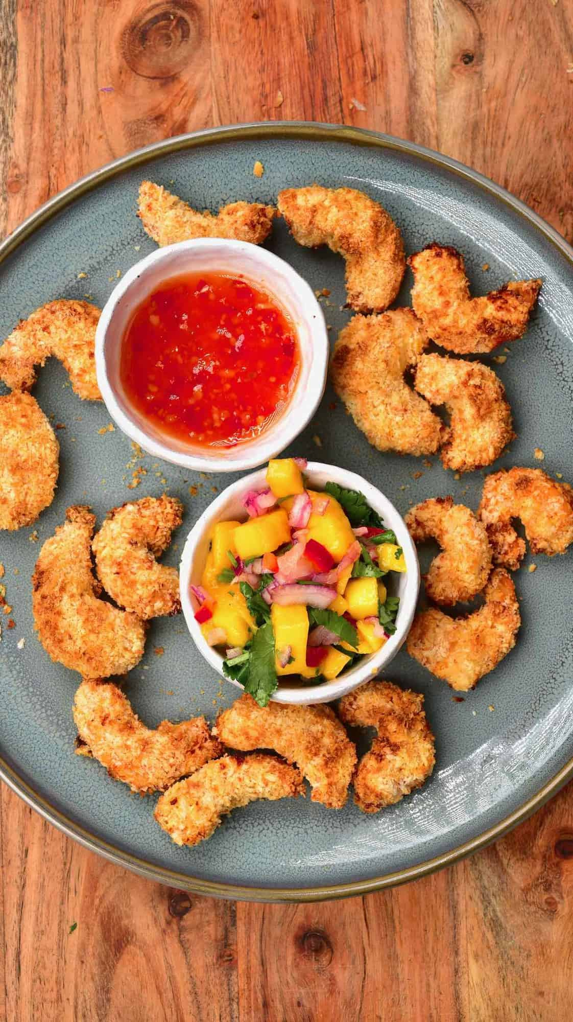 A plate with crispy baked shrimp and two small bowls with chili sauce and mango salsa