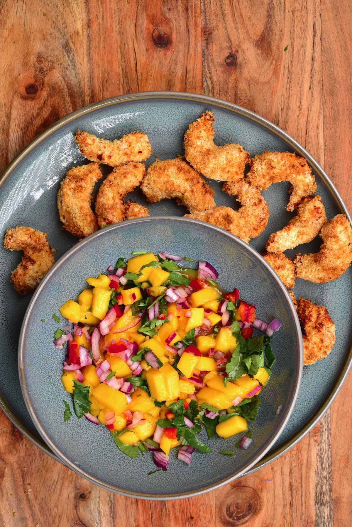 A plate with crispy baked shrimp and a bowl with mango salsa