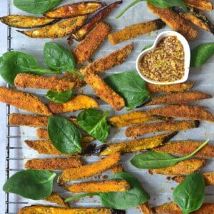 Eggplant baked fries with some spinach leaves and mustard