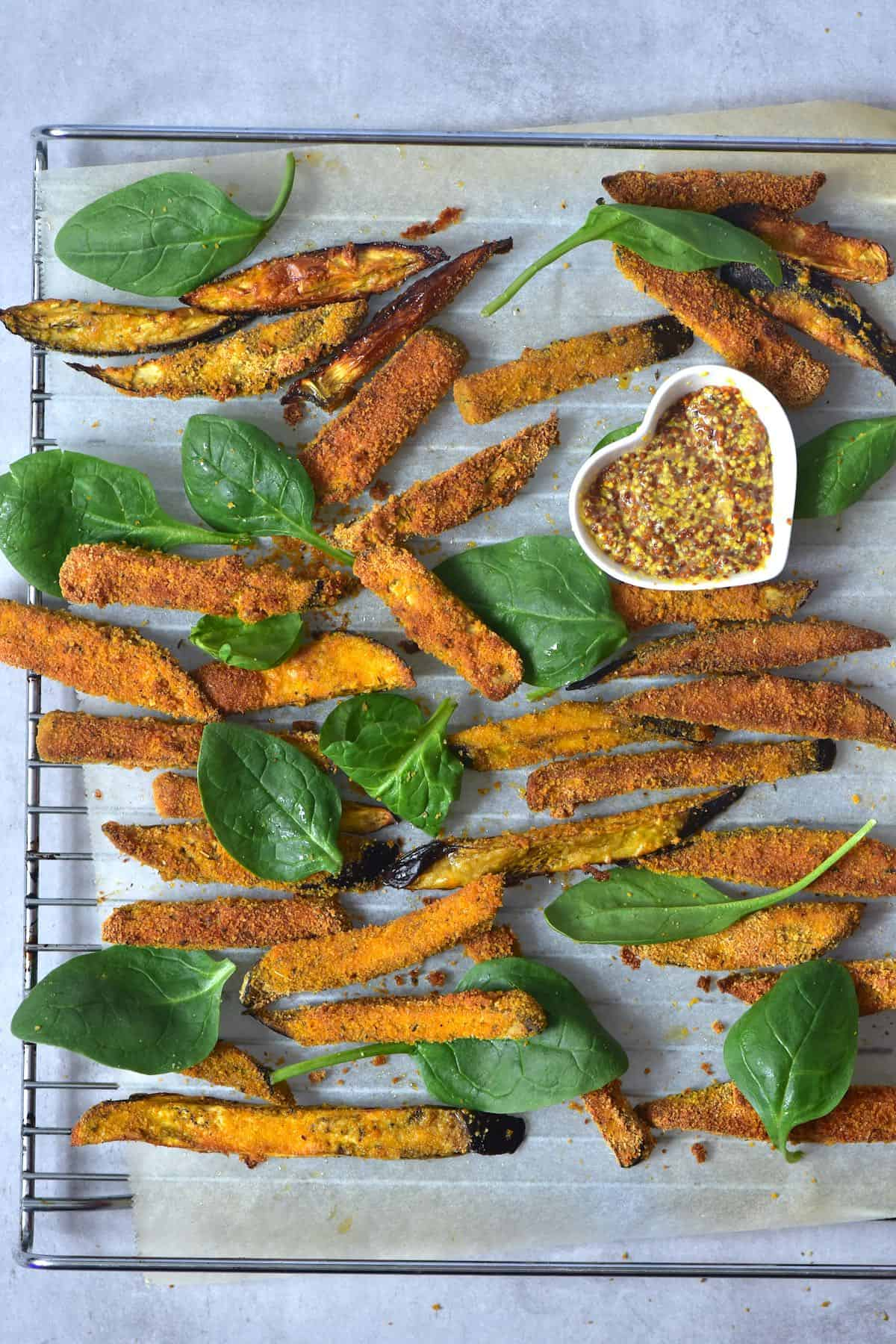 Baked eggplant fries on a baking tray with spinach leaves and mustard