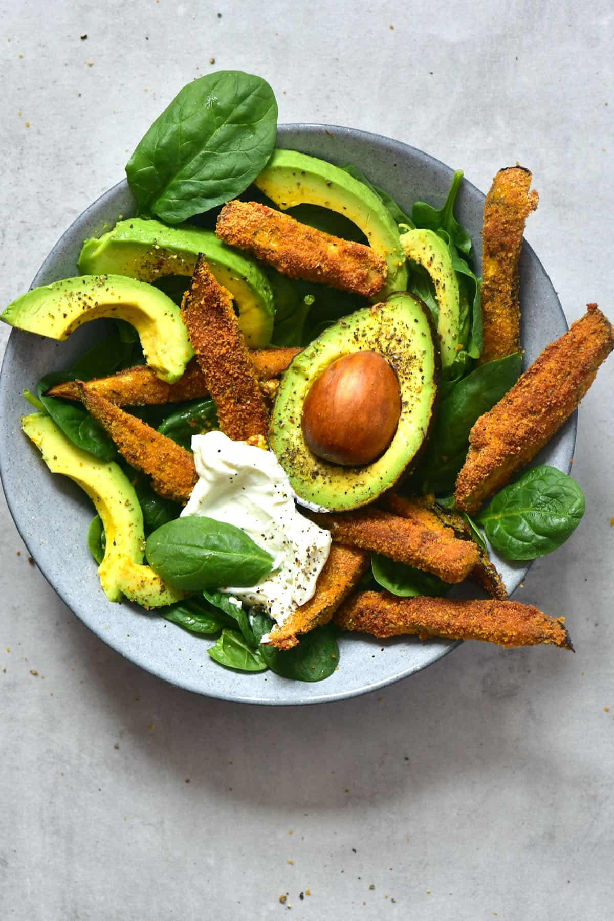 Baked eggplant fries served with spinach and avocado in a bowl