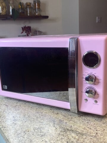 A clean pink microwave on a kitchen island