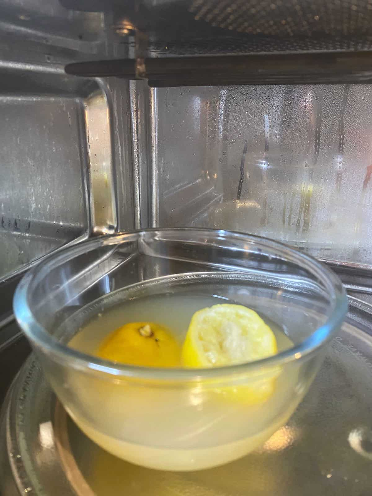 A bowl with water and lemon inside a microwave