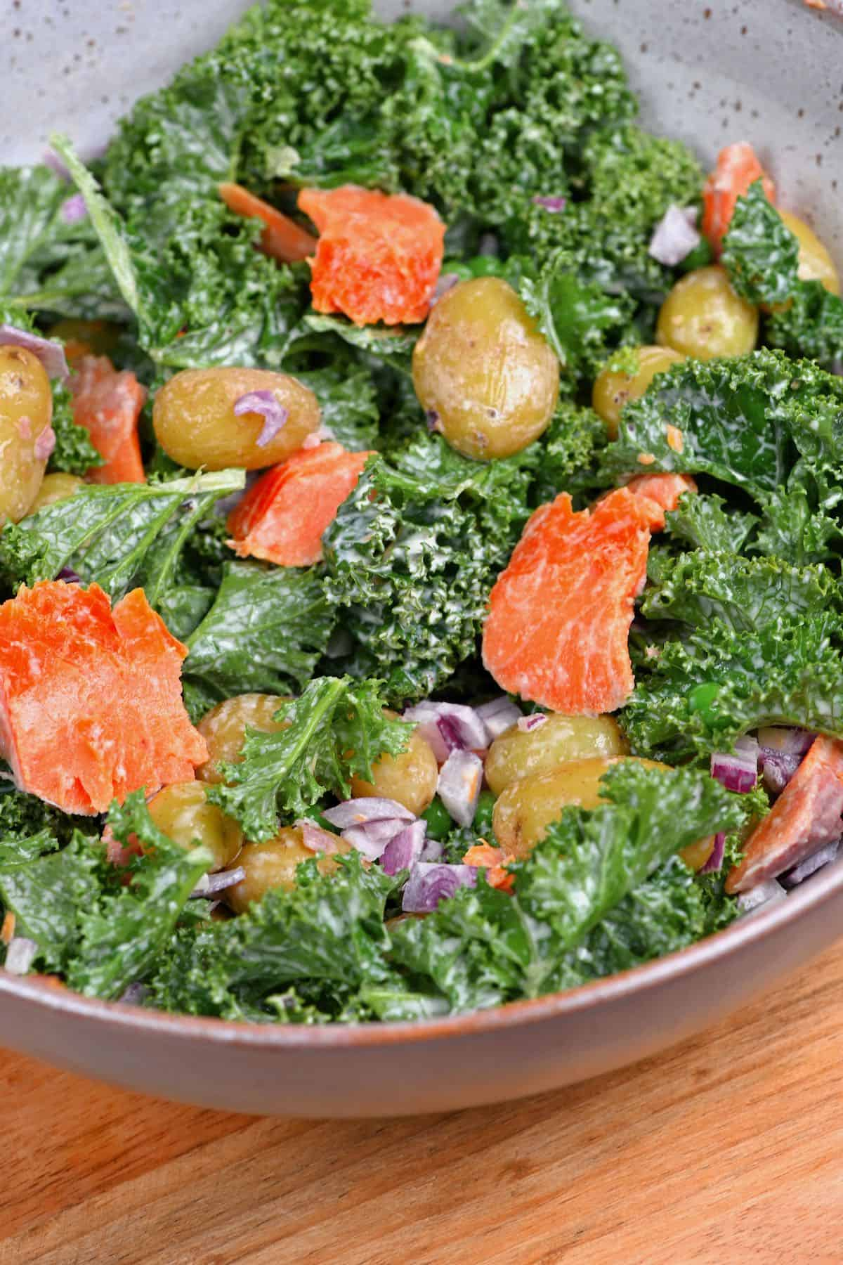 A bowl with potato kale and salmon salad