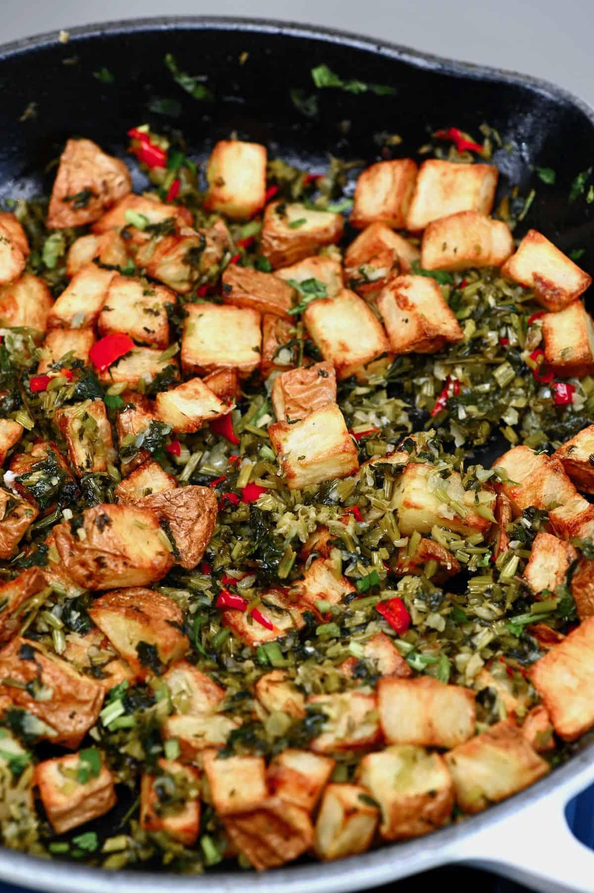 Batata harrah with sautéed cilantro in a pan