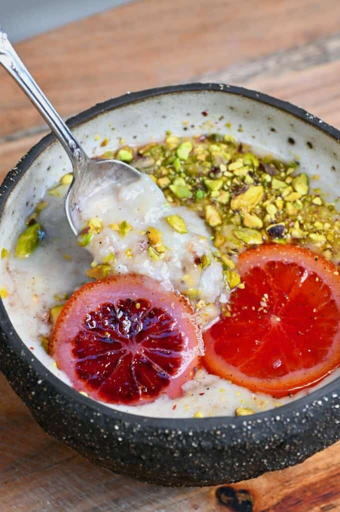 Banana oatmeal in a bowl topped with pistachios and orange slices