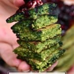 A stack of green spinach pancakes topped with berry compote