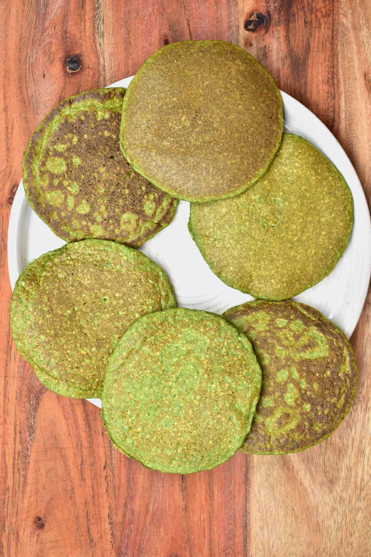 Six green pancakes on a plate