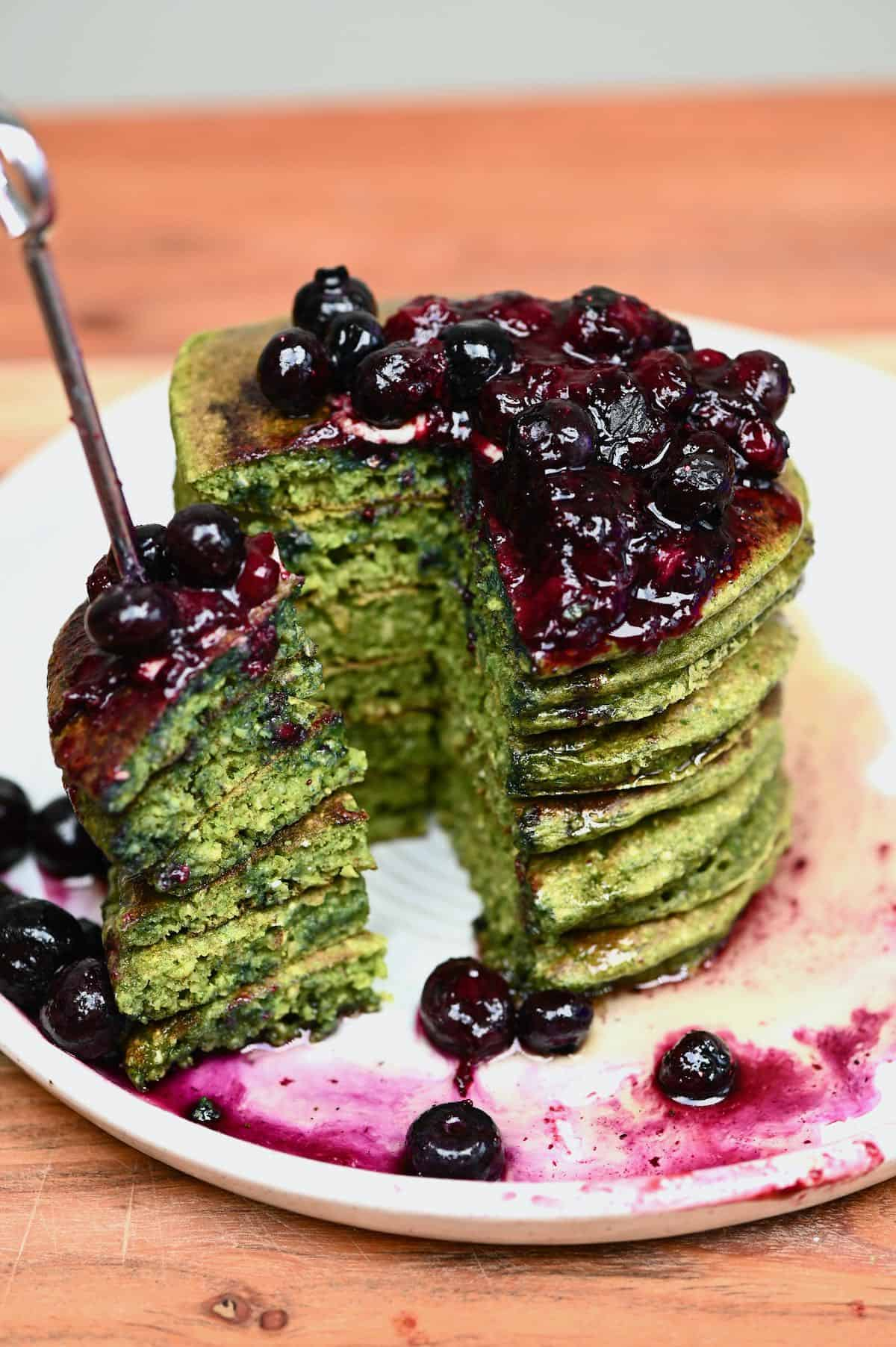 a stack of green pancakes with blueberry compote