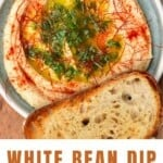White bean dip served in a pale blue bowl topped with paprika and parsley and a piece of bread