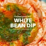 White bean dip served in a pale blue bowl topped with paprika and parsley