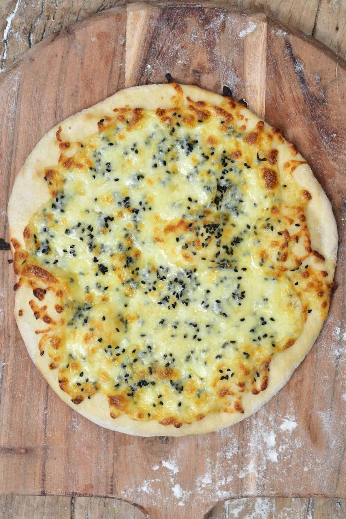 A baked cheese manakish topped with nigella seeds