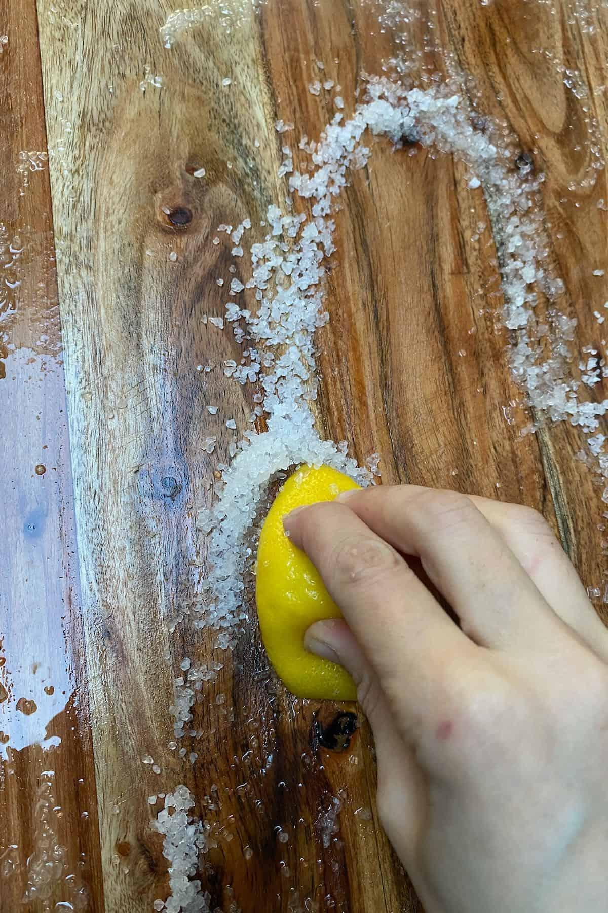 Rubbing lemon with salt on a wooden board