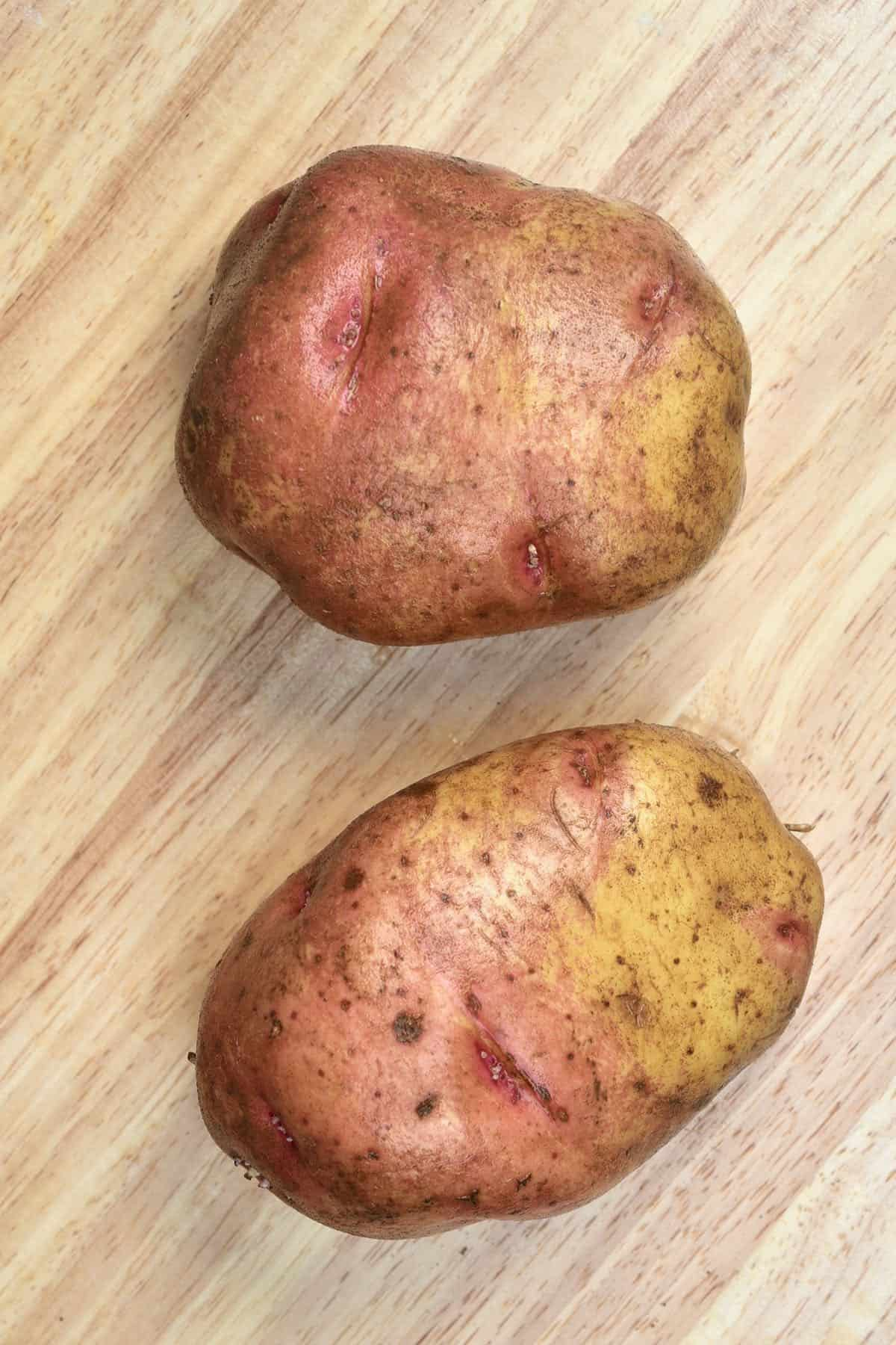 Two large potatoes on a wooden surface