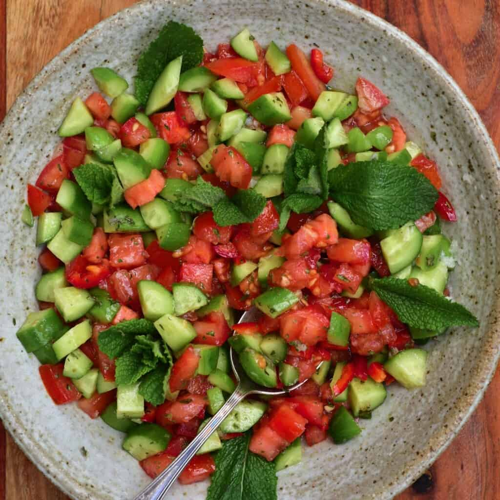 Tomato cucumber salad in a bowl with a spoon
