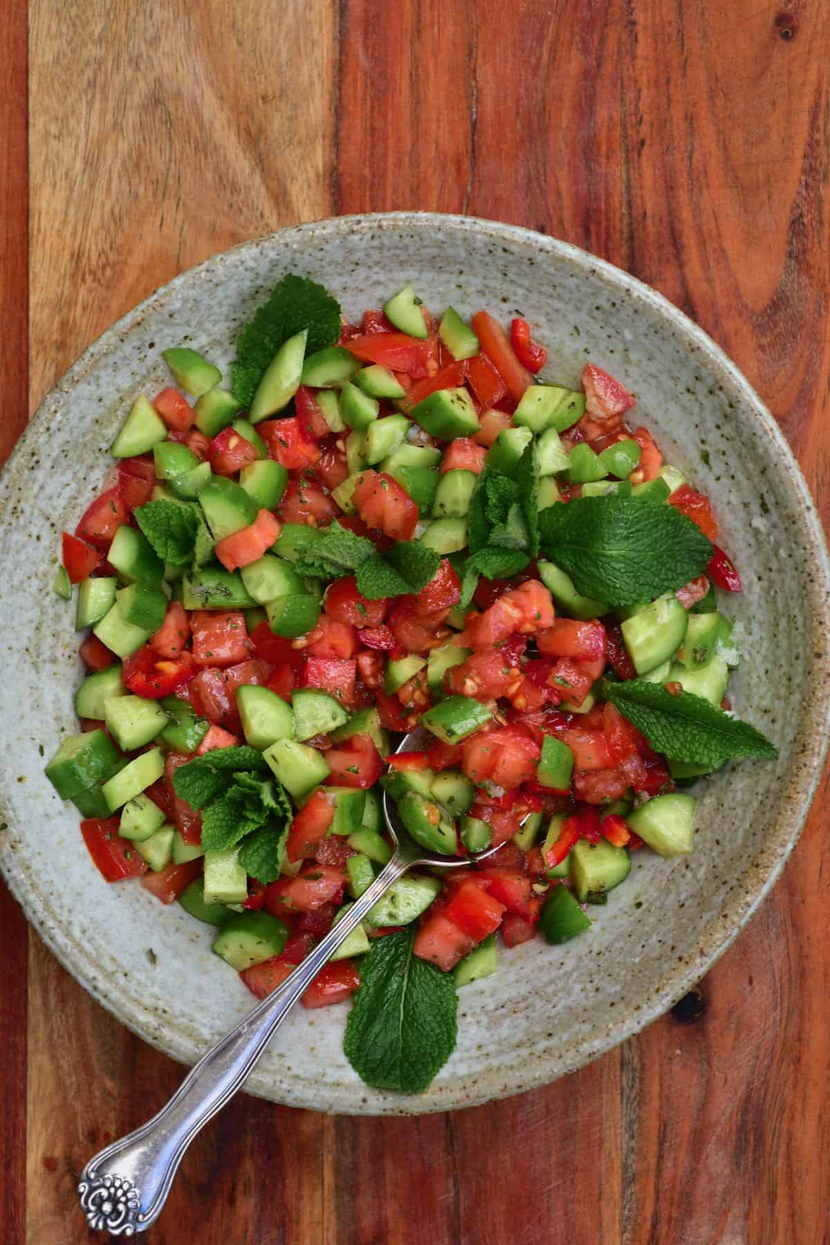 Tomato and cucumber salad topped with fresh mint