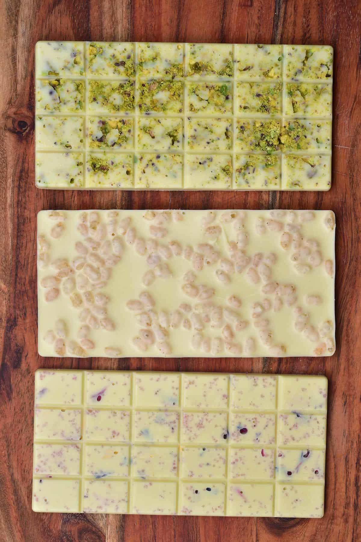Three bars of white chocolate with different toppings - pistachios, puffed rice, edible dried flowers with pink salt