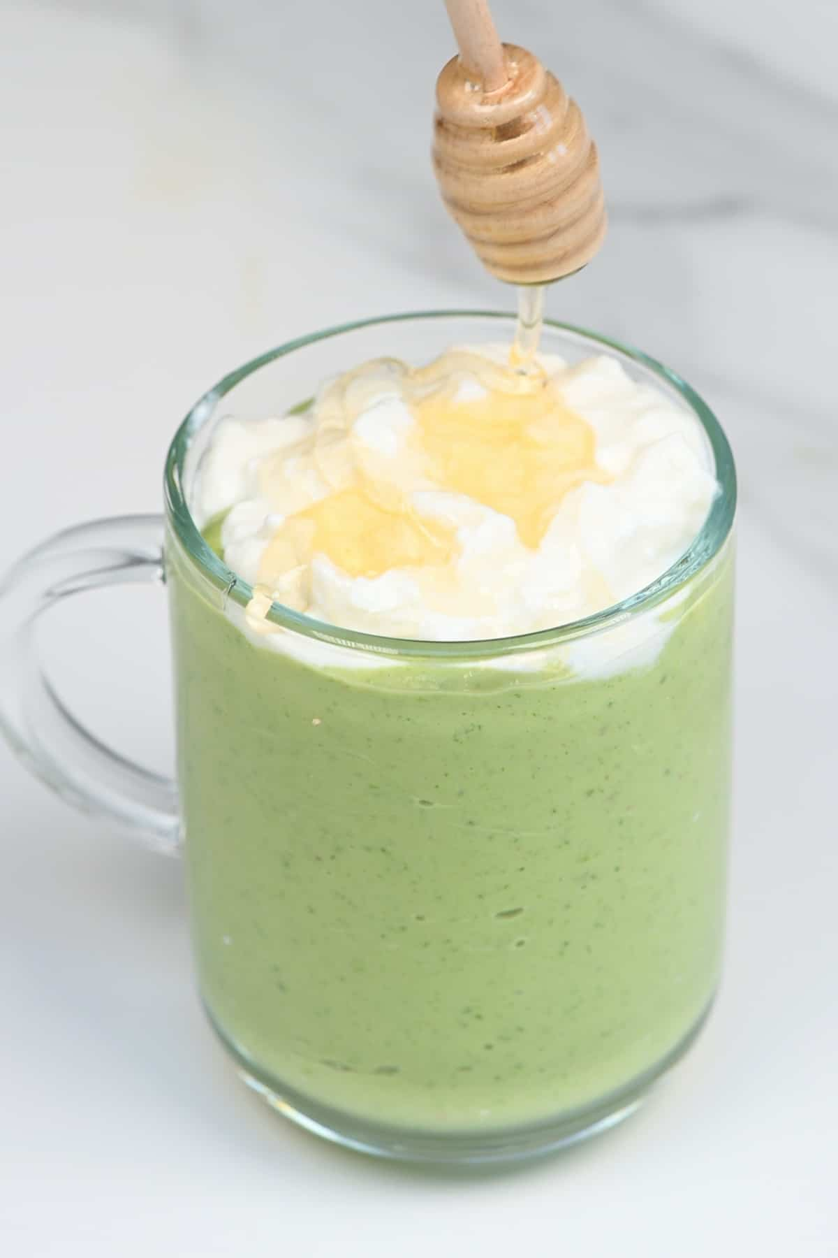Topping an avocado smoothie with honey