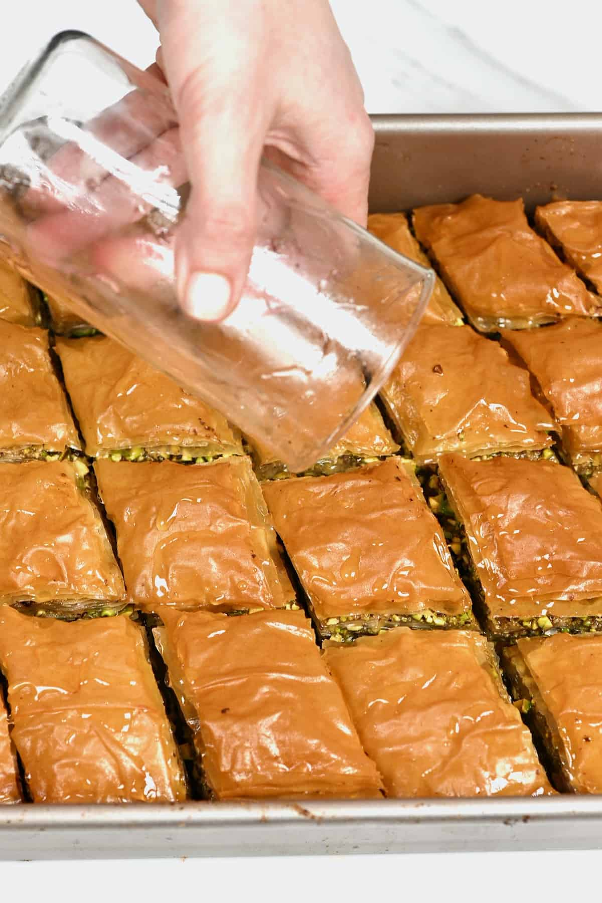 Pouring sugar syrup over freshly baked baklava