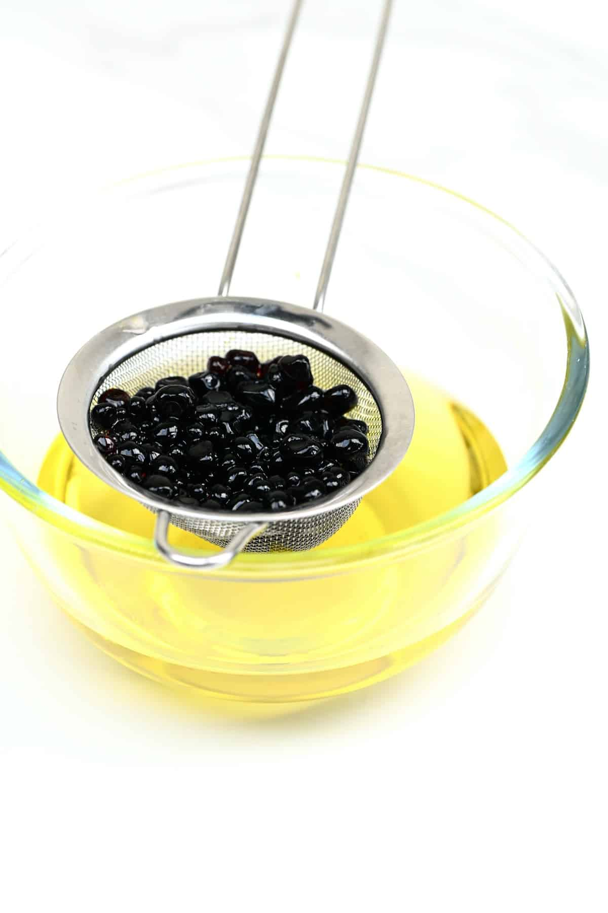 Draining balsamic pearls from the oil