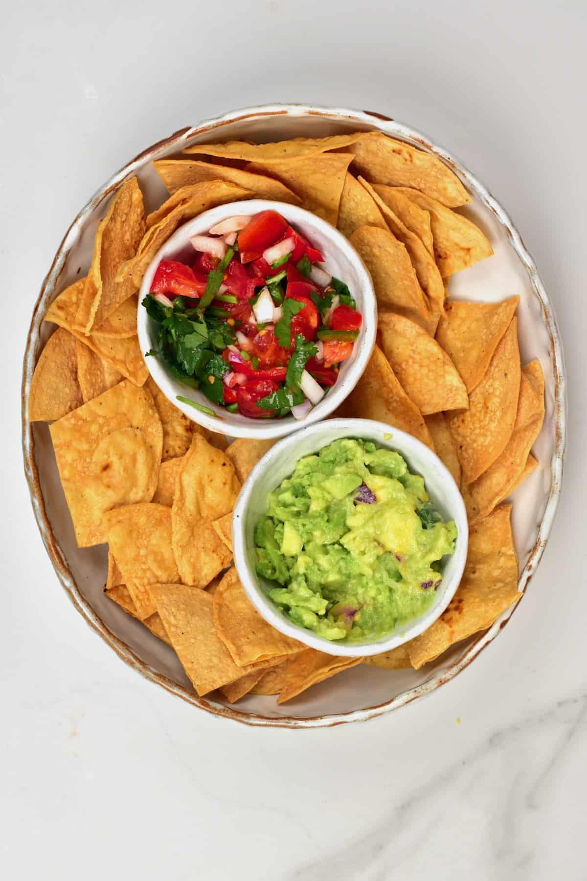 Corn tortilla chips in a bowl with guacamole and pico de gallo