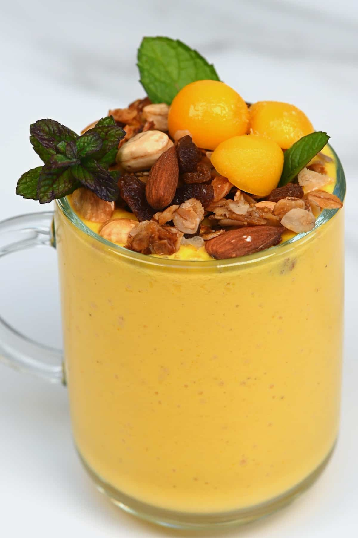 A cup with mango lassi topped with granola