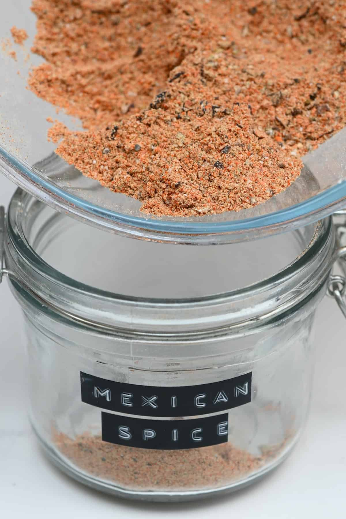 Pouring Mexican spice blend in a jar